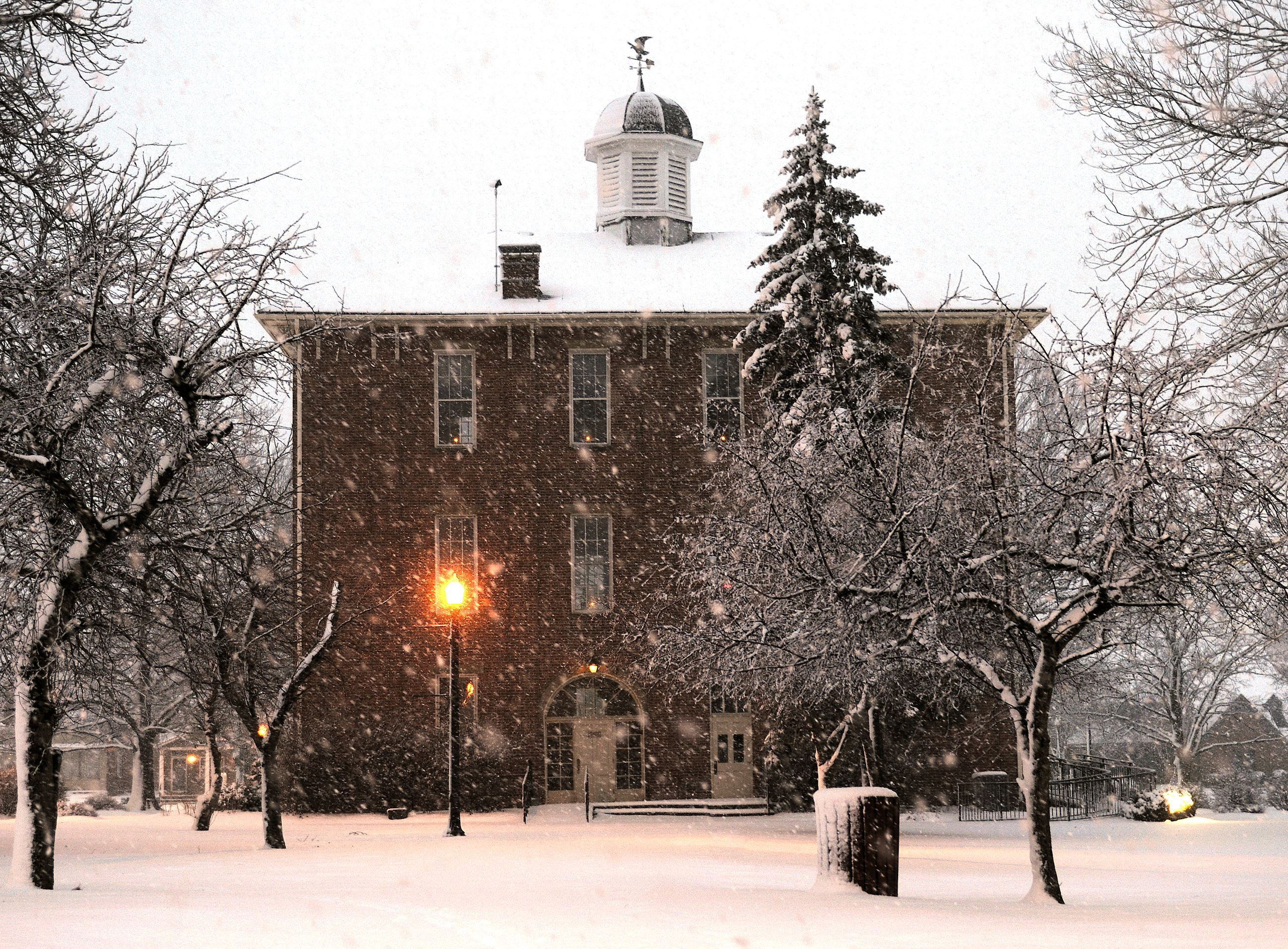 An outside winter view of town hall with snow and lighted lamp